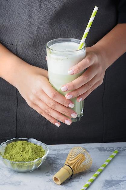 健康的な抹茶ドリンク。バリスタの女の子は、緑茶のラテを手に持っています。 Premium写真