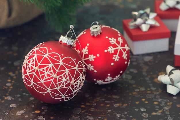 Два красных рождественский бал. в задней части гардероба находятся новогодние подарки в размытости. выборочный фокус Premium Фотографии