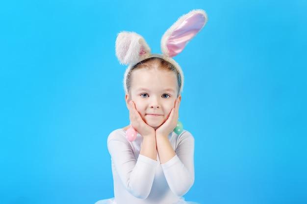 白いイースターバニースーツの少女。美しい感情的な子。 Premium写真