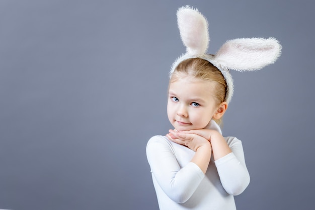 白いウサギの衣装を着た赤ちゃん。コピースペースの近くのウサギの耳を持つかわいい女の子。 Premium写真