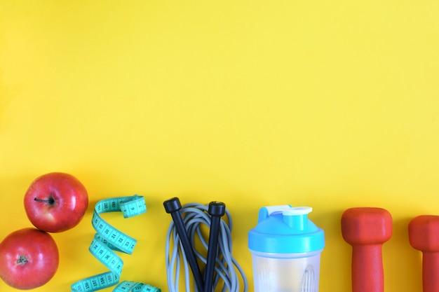 テキストのための場所とフィットネスの背景。黄色の背景にスポーツ用品。 Premium写真