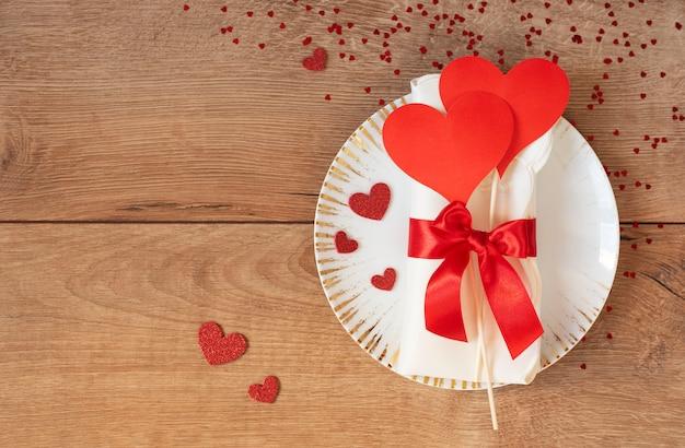 バレンタインデーのお祝いテーブルセッティング。心と木製のテーブルの上の赤の弓と黄金のプレート。テキストのためのスペース。上面図 Premium写真