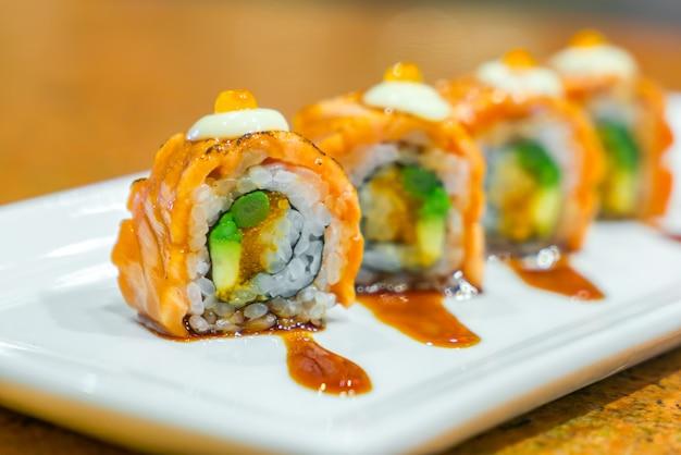 白いプレート上の新鮮な生鮭と日本の寿司ロール。 無料写真