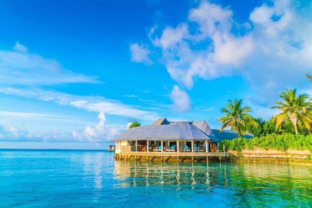 Красивые водные виллы на тропическом острове мальдивы во время восхода солнца Бесплатные Фотографии