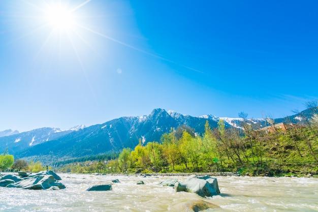 カシミール州、インドの美しい川と雪の山々の景観。 無料写真