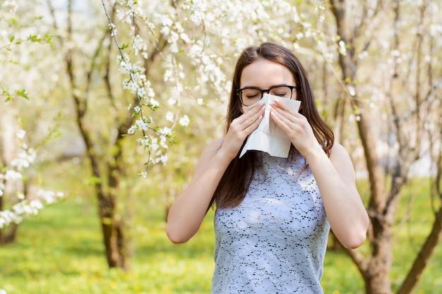 白いナプキンを保持し、咲く木の花粉のアレルギーのためくしゃみをする公園でアレルギーの若い女の子の肖像画 Premium写真