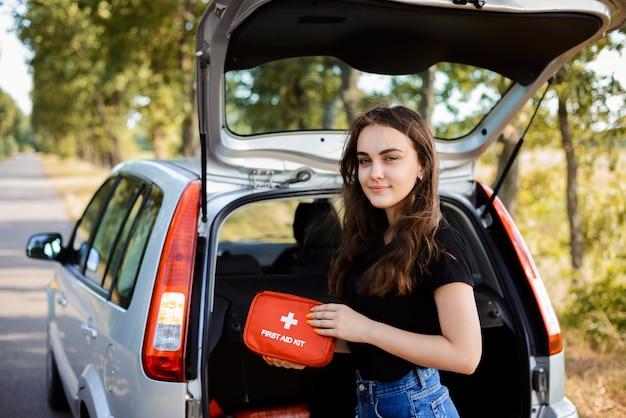 Молодая девушка стоит возле открытой задней двери серебряного хэтчбека и показывает аптечку, которая должна быть в каждой машине на случай чрезвычайной ситуации Premium Фотографии