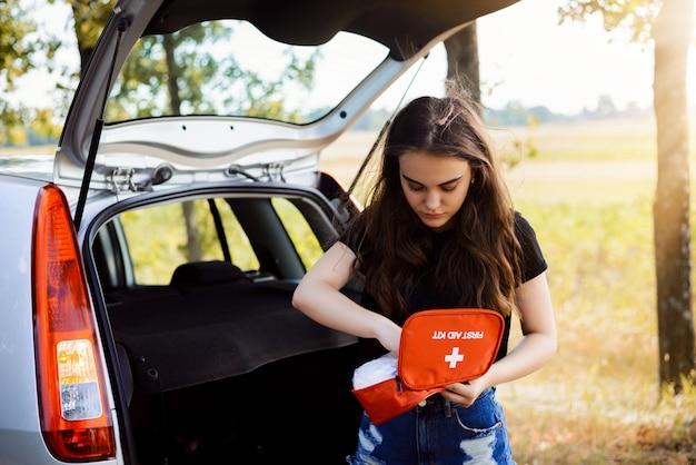 若い魅力的な女の子が開いているバックドアと非常灯が付いている車の近くに立って、応急処置キットで何かを見つけようとします Premium写真