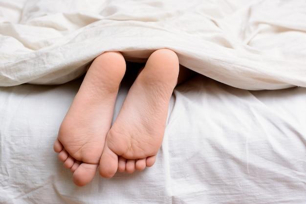 小さな女性の子供はベッドで眠り、毛布の下から素足が見える Premium写真