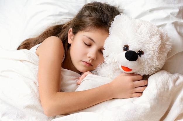 ベッドでテディベアと寝ている長い髪のかわいい女の子 Premium写真