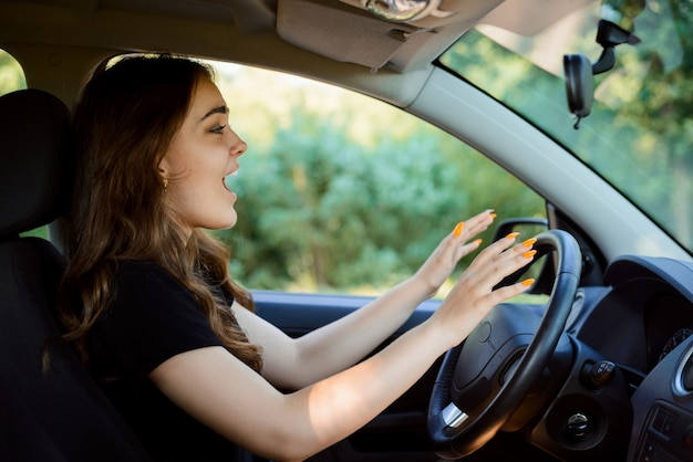 口を開けて車に座っていると、車のクラッシュの前に泣いている少女ドライバー。 Premium写真