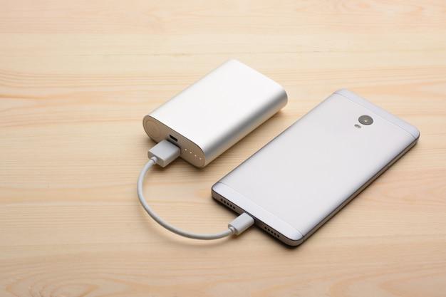 モダンなシルバーのスマートフォンは、パワーバンクで充電しながら背面パネルを上にして明るい木製テーブルの上に置きます Premium写真