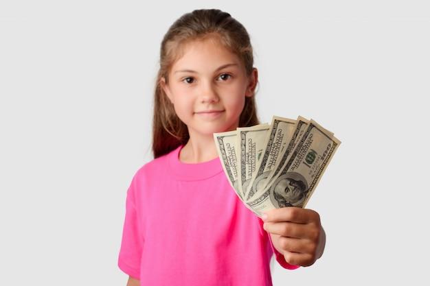 Улыбающаяся маленькая девочка засунула пачку денег в камеру Premium Фотографии