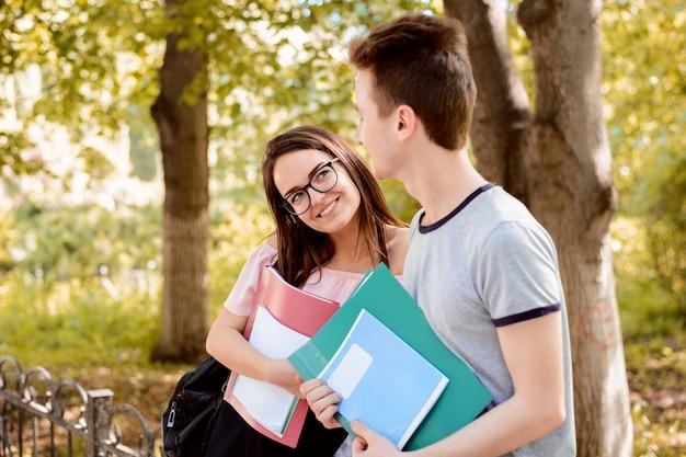 Влюбленная студентка смотрит на красивого одноклассника в парке, заигрывает с ним Premium Фотографии