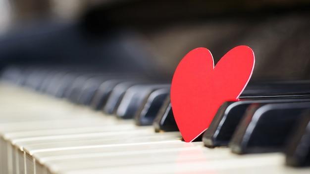 Маленькое красное бумажное сердечко на клавишах пианино Premium Фотографии