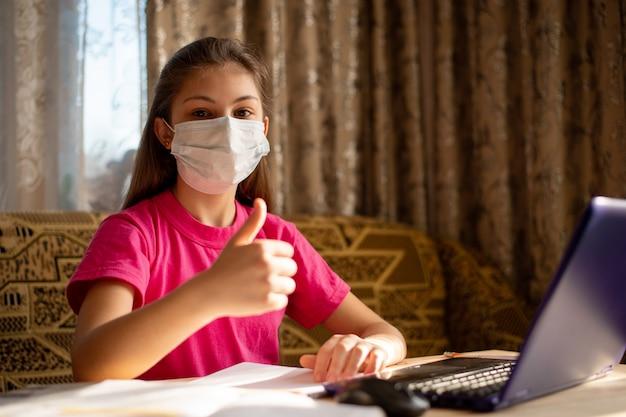 親指を現して医療用マスクを身に着けている若い女子高生、自宅でクラスを持っていることを喜んでいる、遠隔学習をしていて学校に行かない。コロナウイルス検疫中の生活の概念 Premium写真