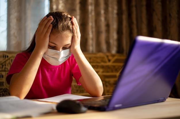 Скучно студент работает за компьютером. молодой школьник учится дома, устал от учебы через интернет целый день Premium Фотографии