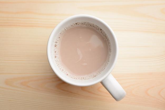 Чашка горячего какао с молоком стоит на деревянный стол Premium Фотографии
