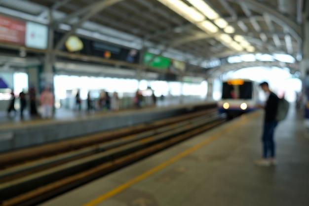 ぼやけて待っている旅行者とスカイトレインプラットフォーム Premium写真