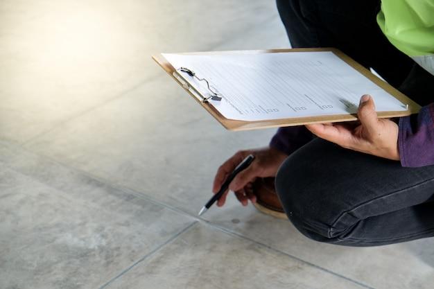 検査官またはエンジニアが床の外観を確認および検査し、表面を指しています Premium写真