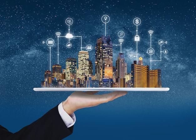 Умный город, строительные технологии и риэлторский бизнес. бизнесмен держа цифровую таблетку с голограммой зданий и технологией интерфейса прикладного программирования Premium Фотографии