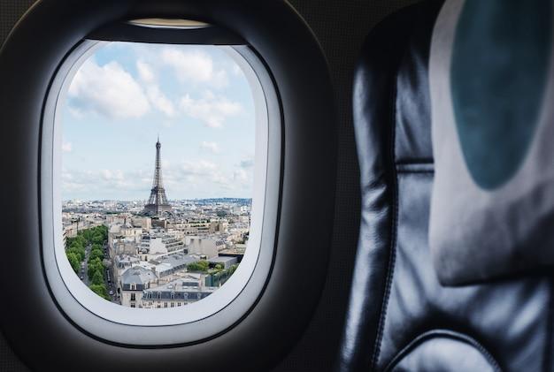 フランス、パリの有名なランドマークとヨーロッパの旅行先を旅行します。飛行機の窓から空撮エッフェル塔 Premium写真