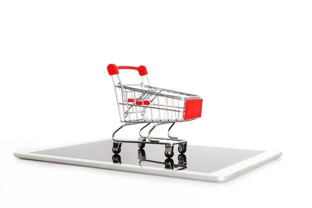 デジタルタブレット、白で隔離されるの空っぽのショッピングカート Premium写真