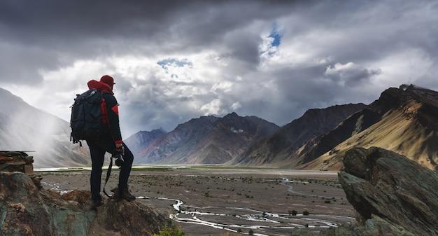 山の景色と雲の切れ間からの日光と崖の上に立ってカメラを保持しているバックパックを持つ男。 Premium写真