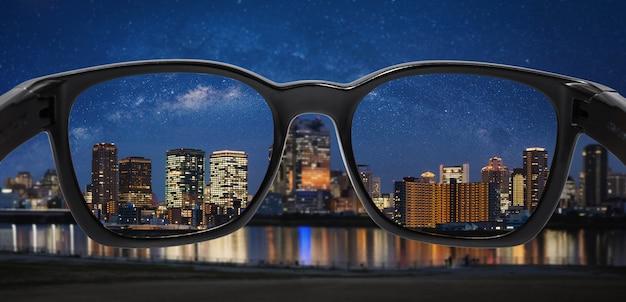メガネを通して星空と夜の街を見る Premium写真