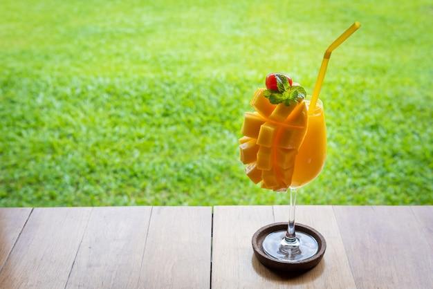 木製のテーブルの上のガラスのマンゴースムージー Premium写真