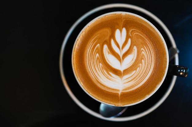 黒いテーブル、黒いトーンの黒いカップでラテアートコーヒー Premium写真