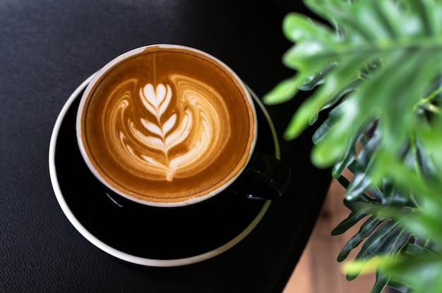 テーブルの上の植物の葉と黒のカップでラテアートコーヒー Premium写真
