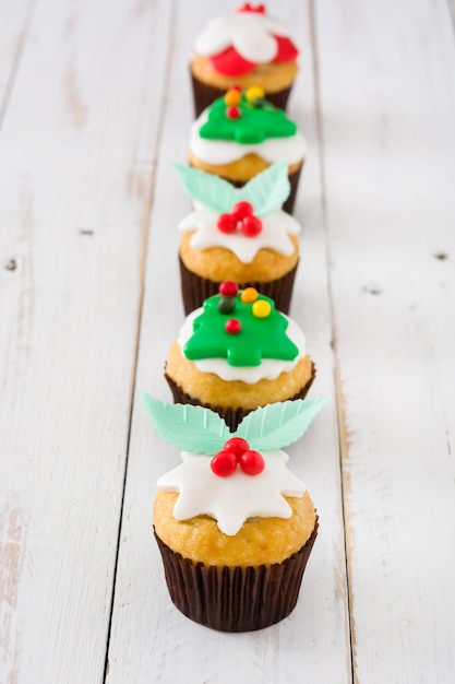 Рождественские кексы на белом деревянном столе Premium Фотографии