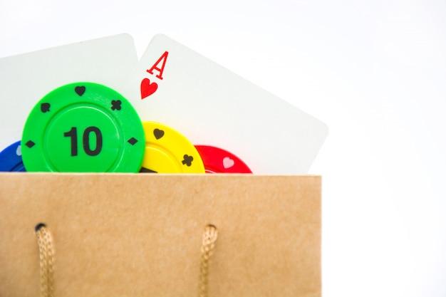 Покер карты и фишки для покера в сумке на белом фоне Premium Фотографии
