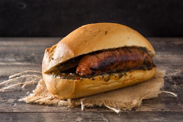 チョリパン。木製のテーブルにチョリソとチミチュリソースの伝統的なアルゼンチンサンドイッチ Premium写真