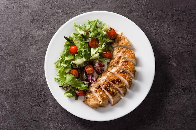 黒のトップビューで皿に野菜と鶏胸肉のグリル Premium写真