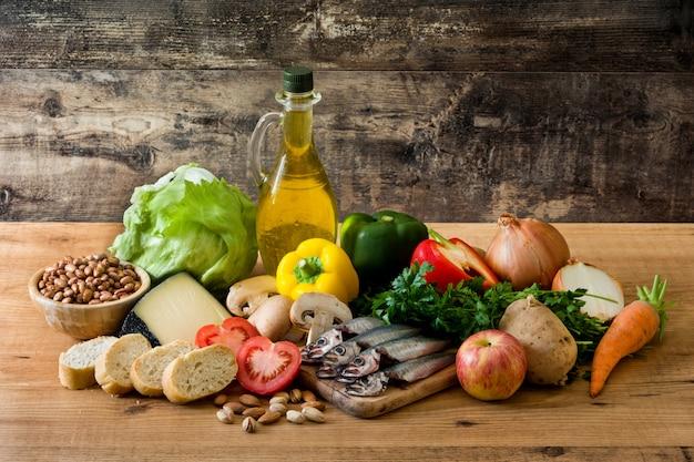 健康的な食事。地中海ダイエットフルーツ、野菜、穀物、ナッツオリーブオイル、木製のテーブルの魚 Premium写真