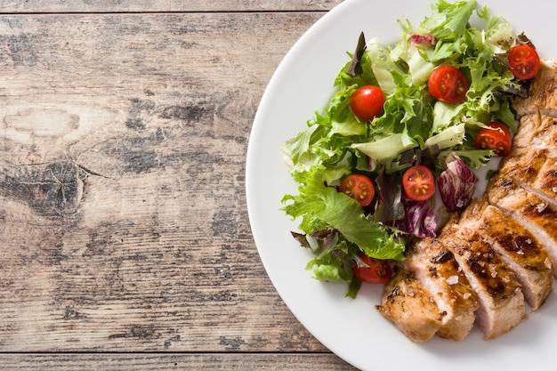 木製テーブルの上の皿に野菜と鶏の胸肉のグリル。トップビュー。コピースペース Premium写真