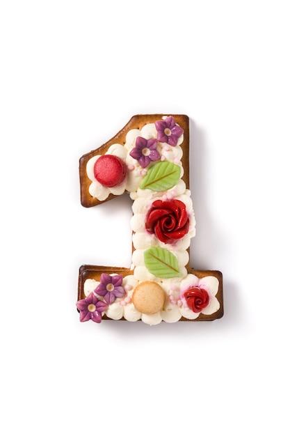 花と白のマカロンで飾られたナンバーワンのケーキ。 Premium写真