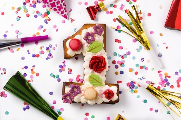 花と紙吹雪のクッキーで飾られたナンバーワンのケーキ Premium写真