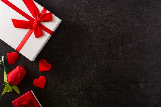 赤いハートと赤いバラで飾られたギフトボックス Premium写真