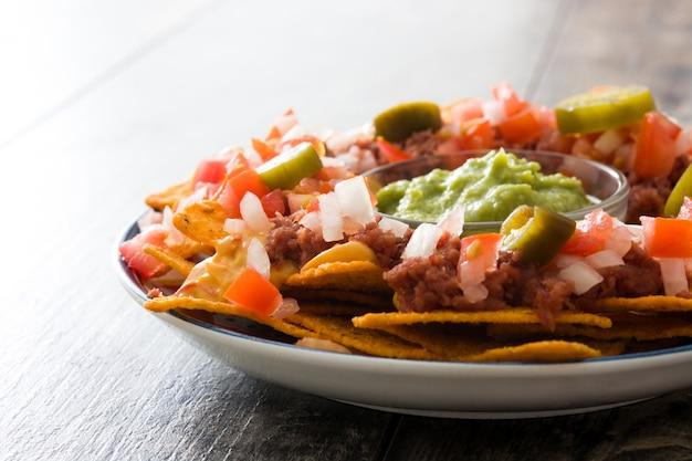 メキシコのナチョス、牛肉、ワカモレ、チーズソース、ピーマン、トマト、木製テーブルの上の皿にタマネギ Premium写真