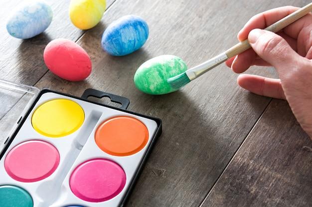 Роспись пасхальных яиц на деревянном столе Premium Фотографии