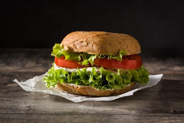 Овощной бублик бутерброд с помидорами, листьями салата и сыром моцарелла на деревянный стол. Premium Фотографии