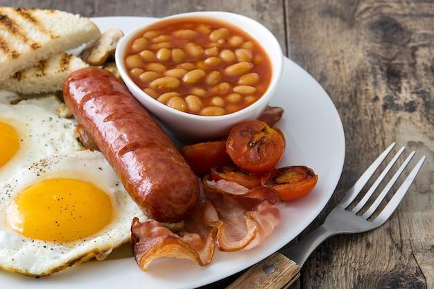 Традиционный полный английский завтрак с яичницей, сосисками, фасолью, грибами, жареными помидорами и беконом на деревянной поверхности. Premium Фотографии
