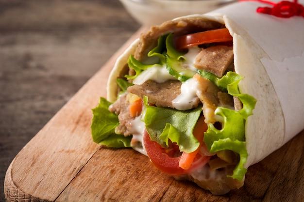 木製のテーブルにドネルケバブまたはシャワルマのサンドイッチ。 Premium写真