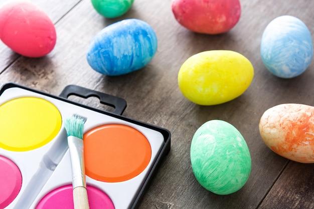 Красочные пасхальные яйца на деревянном столе Premium Фотографии