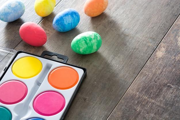 Красочные пасхальные яйца на деревянный стол копией пространства Premium Фотографии