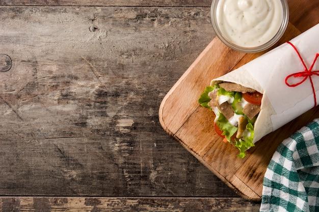 木製のテーブルトップビューコピースペースにドネルケバブまたはシャワルマサンドイッチ Premium写真