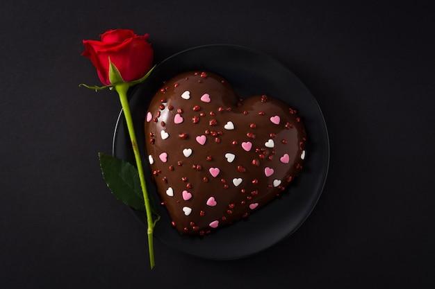 Торт в форме сердца и красная роза на день святого валентина Premium Фотографии